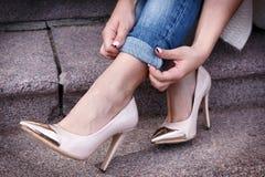在一个美丽的桃子高跟鞋的女性腿有金子的引导 特写镜头 手改正了牛仔裤 免版税图库摄影