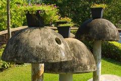 在一个美丽的泰国庭院公园用水泥涂蘑菇,有在上面的盆的花卉植物的 库存图片
