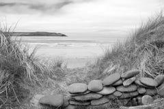 在一个美丽的海滩的石墙风雨棚在黑白 库存图片