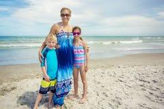 在一个美丽的海滩的逗人喜爱的家庭画象 库存图片