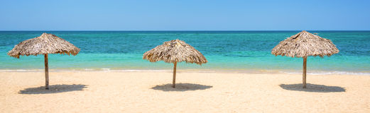 在一个美丽的热带海滩、全景旅行背景、旅行和旅游业概念的秸杆伞 免版税库存照片
