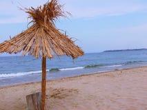 在一个美丽的热带海滩的异乎寻常的海滩秸杆伞 免版税库存照片
