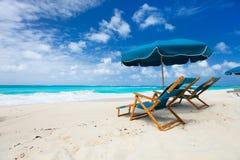 在热带海滩的椅子和伞 库存照片