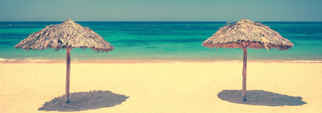 在一个美丽的热带海滩,全景旅行背景,葡萄酒样式的两把秸杆伞 图库摄影