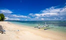 在一个美丽的白色沙子海滩的一条白色舷外架小船 免版税图库摄影