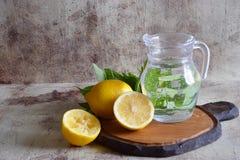 在一个美丽的蒸馏瓶的刷新的柠檬水,柠檬,薄菏芬芳小树枝在桌上的 免版税库存图片