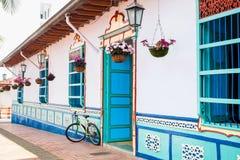 在一个美丽的蓝色和白色房子旁边骑自行车在Guatape 库存照片