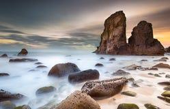 在一个美丽的离开的海滩的金黄日落 免版税库存图片
