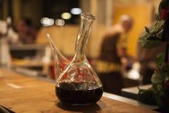 在一个美丽的玻璃玻璃水瓶蒸馏瓶的红色西班牙酒 免版税图库摄影
