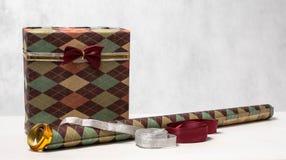 在一个美好的包裹的人的礼物与弓和包装纸 免版税库存照片