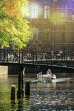 在一个美好的春日期间,游人参观徒步阿姆斯特丹,乘自行车,乘小船, 库存照片
