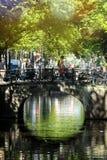 在一个美好的春日期间,游人参观徒步阿姆斯特丹,乘自行车,乘小船, 图库摄影