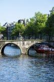 在一个美好的春日期间,游人参观徒步阿姆斯特丹,乘自行车,乘小船, 免版税库存照片