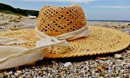 在一个美好的晴天备草粮在沙子的帽子 库存照片