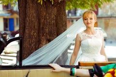 在一个美妙的白肤金发的新娘的一个看法从一辆减速火箭的汽车 免版税库存照片