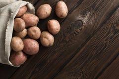 在一个老亚麻帆布袋子的新鲜的土豆在黑暗的木板背景 文本的自由地方 免版税图库摄影