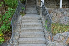 在一个老具体楼梯的石灰色步与在绿色植被中的扶手栏杆 库存照片