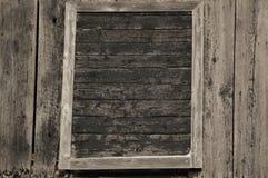 在一个老农舍的墙壁的被构筑的老黑门 免版税库存图片