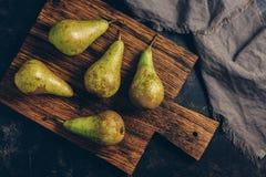 在一个老切板的绿色梨,土气样式定了调子与无言树荫的照片 免版税库存图片