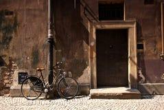 在一个老墙壁和门旁边骑自行车身分 免版税库存图片