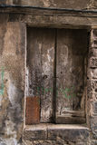 在一个老岩石大厦的木生锈的门 免版税库存照片