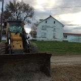 在一个老房子前面的拖拉机 免版税库存照片