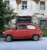 在一个老房子前面的老汽车 库存图片