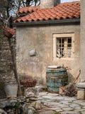 在一个老房子前面的葡萄酒桶在Valun 免版税库存图片