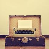 在一个老手提箱的老打字机,有一个减速火箭的作用的 免版税库存照片