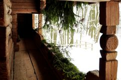 在一个老日志村庄的门廊的白色和绿色假日装饰与云杉的分支和白色圣诞节球的 库存图片