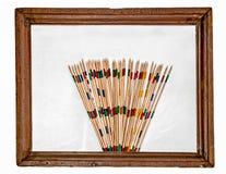 在一个老木制框架的五颜六色的木棍子 库存照片
