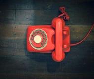 在一个老木地板上的减速火箭的红色电话 库存照片