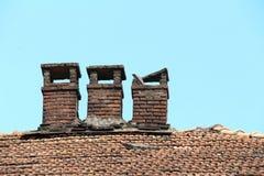 在一个老木房子的瓦屋顶的砖烟囱 免版税库存照片