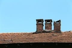 在一个老木房子的瓦屋顶的砖烟囱 库存照片