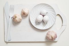 在一个老木板条盘子的白色叉子刀子板材 艺术想法白色蕃茄,绘与油漆 烹调的大蒜 免版税库存照片