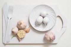 在一个老木板条盘子的白色叉子刀子板材 艺术想法白色蕃茄,绘与油漆 烹调的新鲜的红色toma大蒜 库存照片