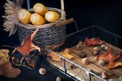 在一个老木盘子、橡子和叶子的秋天构成 土气样式 免版税图库摄影
