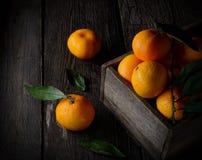 在一个老木箱的新鲜的桔子 在一个木背景 免版税库存照片