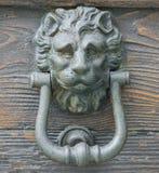 在一个老木门的狮子顶头敲门人 图库摄影