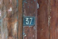 在一个老木门的老金属第37匾 免版税库存照片