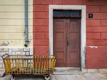 在一个老棕色门前面的老生锈的黄色推车 库存照片