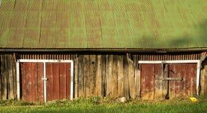 在一个老棚子的红色毂仓大门有一个绿色屋顶的 免版税库存照片