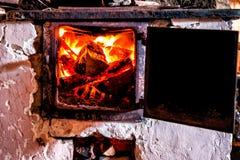 在一个老烤箱的燃烧的木柴 免版税库存图片