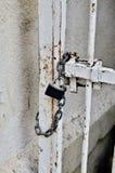 在一个老白色生锈的门的一把锁 免版税图库摄影