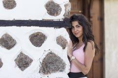 在一个老石墙后的年轻美丽的妇女,室外射击 库存图片