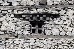 在一个老石墙的木窗口在Manang村庄,喜马拉雅山,尼泊尔 免版税图库摄影