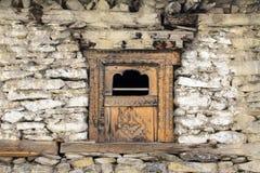 在一个老石墙的木窗口在Manang村庄,喜马拉雅山,尼泊尔 免版税库存图片