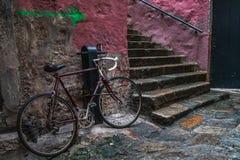 在一个老石小的镇的街道的红色自行车 库存照片