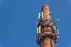 在一个老砖烟囱的电信天线 行业概念 现代技术 输电线在公园 免版税库存图片