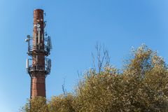 在一个老砖烟囱的电信天线 行业概念 现代技术 输电线在公园 免版税图库摄影